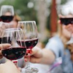 A hand holding a glass of red wine Description automatically generated